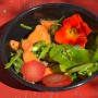 A delicious garden salad brunch containing beets, miners lettucs and flowers